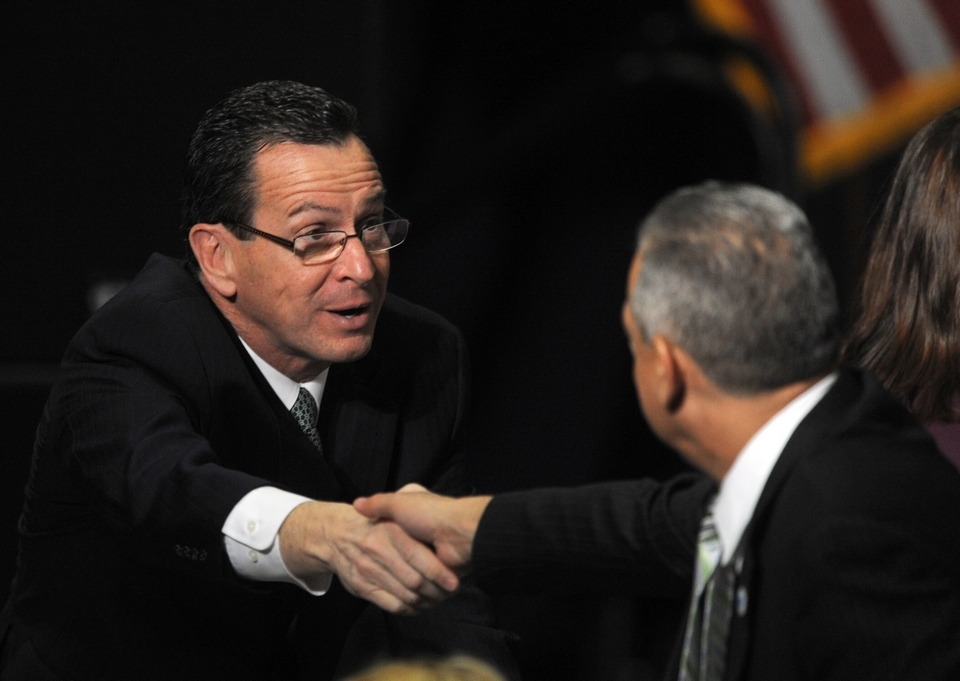 Gov. Dannel P. Malloy reaches over to the shake the hand of an attendee prior to the arrival of Vice President Joe Biden. Malloy released details on his proposal for new gun laws.