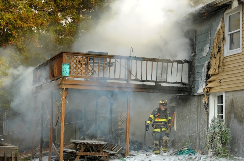 Old Mystic firefighters are seen silhouetted against the smoke as they battle a house fire at 154 Breezy Knoll Drive Wednesday morning. Oct. 30, 2013.  The fire was reported just before 10 a.m. with heavy fire showing from the rear of the home when the Old Mystic Fire Department arrived on scene.
