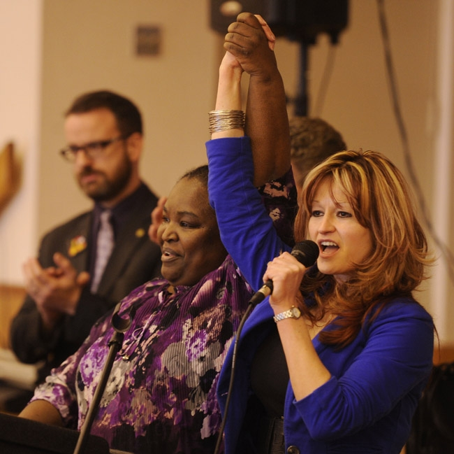 Stephanie Johnson, left, and Lisa D'Abrosca, presidents respectively of the technicians and nurses unions at L+M hold their hands high as they address the union members in attendance at a press conference/rally preceding a membership meeting at the Port and Starboard ballroom at Ocean Beach Park Wednesday, Dec.18, 2013.