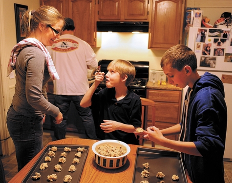 Kristin Baker, left, watches Monday as son, Ben, 10, samples the cookie dough and Mikey, 12, places dough on baking sheets in their Norwich kitchen, in preparation for a family Thanksgiving reunion.