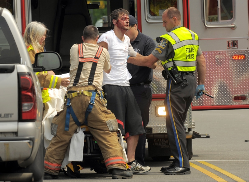 A man is taking into custody by Connecticut State Police and emergency crews for transport to the hospital at the scene of a multiple car accident, possibly resulting from a police chase at the intersection of routes 85 and 161 in Chesterfield Tuesday June 18, 2013.  A LifeStar helicopter was called to the scene to transport one of the victims.