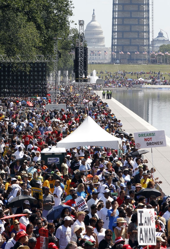 People crowd around the Reflecting Pool at they attend a rally to commemorate the 50th anniversary of the 1963 March on Washington on Saturday, Aug. 24, 2013, in Washington.