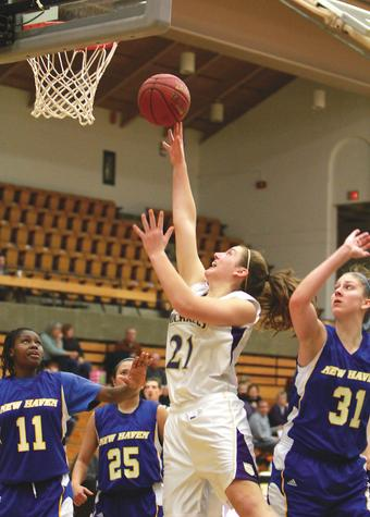 Former Waterford great Alexa Long (21) goes up between three New Haven defenders for a basket during a recent St. Michael's College game in Colchester, Vermont.