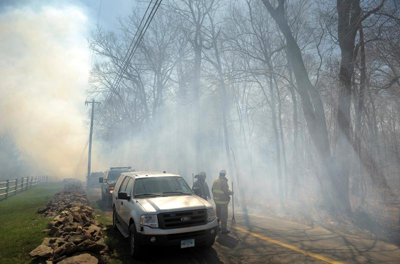 Firefighters with the Connecticut Department of Energy and Environmental Protection work on containing a major woods fire at Devils Hopyard State Park Tuesday March 27, 2012