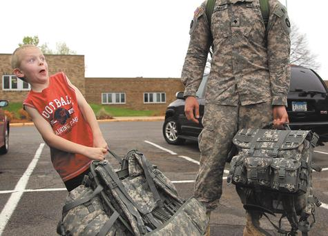 Specialist David Passmore of Burnsville, Minn., gets a hand carrying his bag from his cousin Jarrett Wood, 7, at the Bloomington Armory in Bloomington, Minn., on Sunday. Two hundred fifteen Minnesota National Guard soldiers of the 1st Squadron, 94th Cavalry, 1st Brigade Combat Team were scheduled to return on Sunday to Minnesota after serving in Iraq.