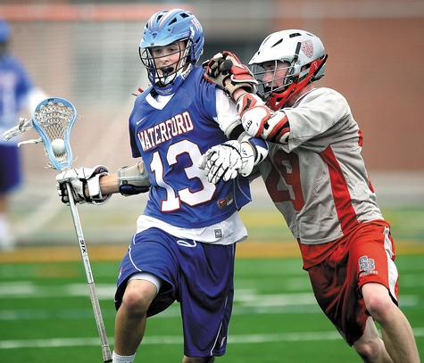 Waterford's Ryan Brouwer (13) attempts to elude St. Bernard's Eric Brown during Wednesday's ECC Small Division boys' lacrosse game at Waterford. Brouwer became only the second player in program history to reach 100 career points in the Lancers' 18-3 victory over the Saints.
