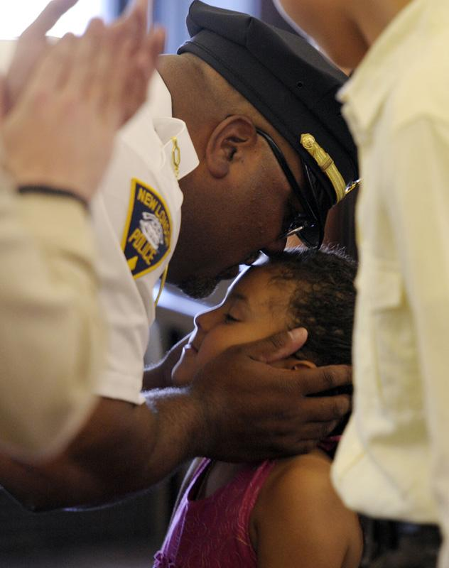 Newly sworn-in New London Police Captain Brian Wright bends to give his daughter Brielle, 5, a kiss after he was sworn-in during a ceremony Friday, June 29, 2012 in the city council chambers.Wright and fellow new Captain Todd Bergeson were sworn-in by Mayor Daryl Justin Finizio.
