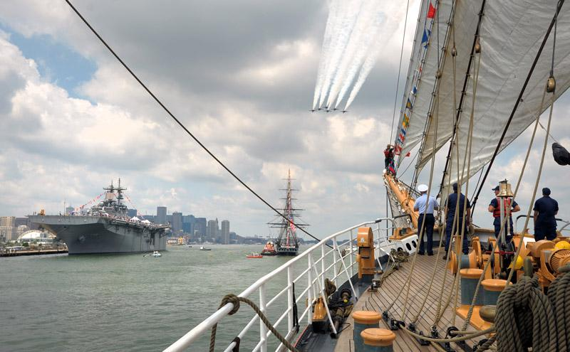 The U.S. Navy Blue Angels perform a fly-by of the USS Wasp, left, USS Constitution, center, and the United States Coast Guard Barque Eagle as the Eagle joins the USS Constitution on the Constitution's annual 4th of July turn-around cruise in Boston Harbor Wednesday, July 4, 2012.