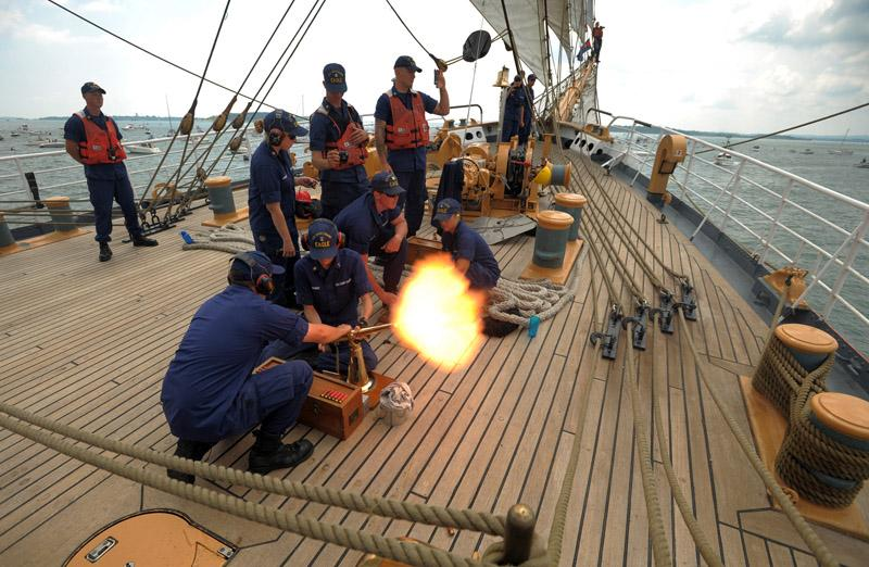 The crew of the United States Coast Guard Barque Eagle fires a 21-gun salute as the Eagle joins the U.S.S. Constitution on the Constitution's annual 4th of July turn around cruise in Boston Harbor Wednesday, July 4, 2012.
