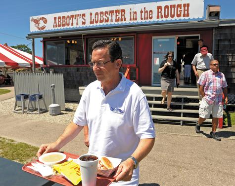 Gov. Dannel P. Malloy carries his lunch - a lobster roll, chips and clam chowder - to his table Wednesday during a stop at Abbott's Lobster in the Rough in Noank.