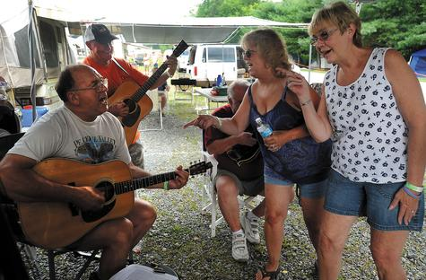 Yvonne Sekscenski, right, of Higganum, and Janet Jacobson of Kensington join Larry Bartlett, left, of Wallingford in singing the chorus of 'She's No Angel' with Joe Arsenault of Winchester, N.H., at Dodd Stadium in Norwich on Thursday. The four gathered with a group of friends for a jam session at the campground that has popped in the parking lot for the opening day of the Podunk Bluegrass Festival. The festival is taking place through Sunday. The friends travel and camp together as they have traveled to several bluegrass festivals in the New England area each summer since the early '90s.