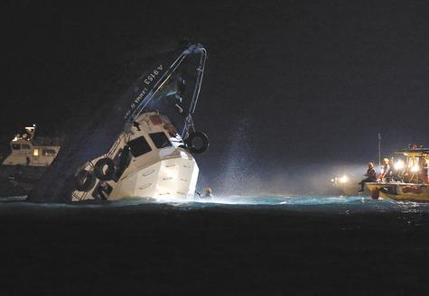 Rescuers check on a half-submerged boat after it collided Monday night with a ferry near Lamma Island, off the southwestern coast of Hong Kong. Authorities said 25 people were killed and dozens more were injured. The boat was carrying staff members of a utility company and their family members to Hong Kong's famed Victoria Harbour to watch a fireworks display on the long holiday weekend celebrating China's National Day and mid-autumn festival.