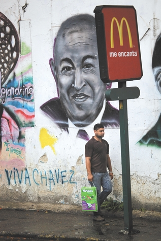 A pedestrian walks past a mural of Venezuela's President Hugo Chavez in Caracas on Friday. Venezuelans head to the polls Sunday to vote in their country's presidential election, deciding on whether to keep Chavez or seek change with opposition candidate Henrique Capriles.