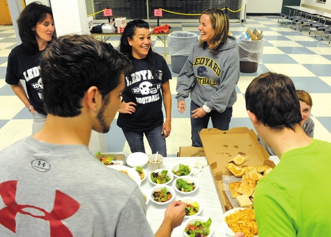 Kristie Perry, center, Krista Rainey, right, and Jenny Gill, left, chat while serving lunch to Ledyard High football players in the high school cafeteria on Thursday.
