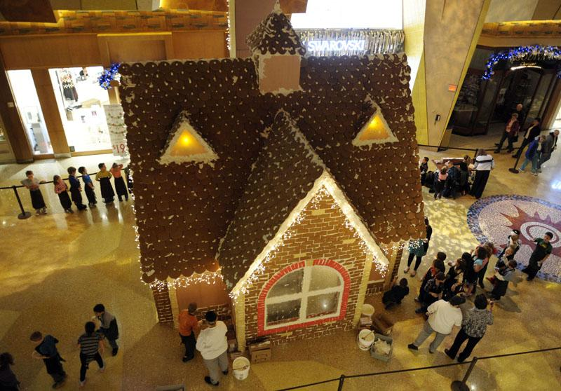 Second-grade students from Charles Murphy Elementary School in Montville help Mohegan Sun Executive Pastry Chef Lynn Mansel and his team decorate the casino's annual giant gingerbread house Monday, Nov. 19, 2012, on the retail concourse at Mohegan Sun.