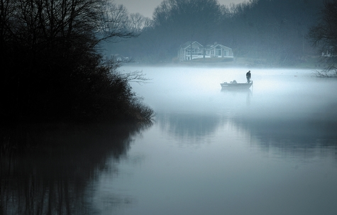 A man goes for a late afternoon fishing trip Tuesday as a layer of fog and mist gather on Gorton Pond in East Lyme.