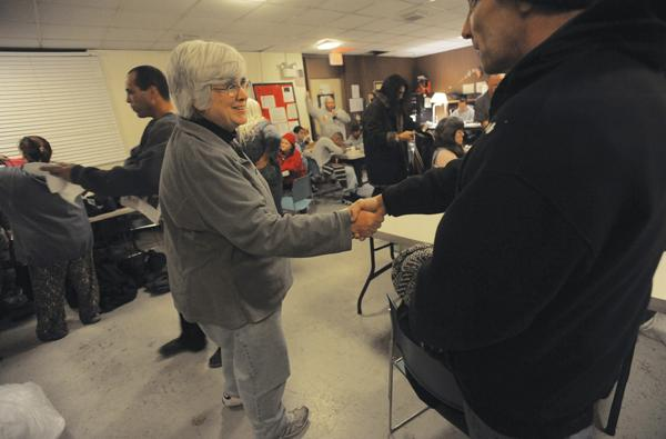 Cathy Zall is thanked by a client as she works at the overnight shelter at St. James Episcopal Church in New London.