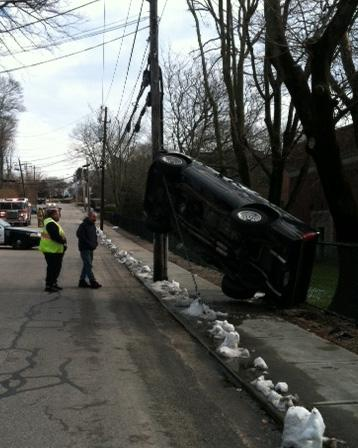 Two Westerly High School students escaped injury late Thursday morning, when their pickup truck flipped on John Street in Westerly and ended up hanging from a utility pole guy wire.