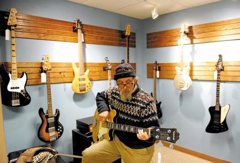 Jake Kaeser tries-out an Epiphone Jack Casady Signature series bass guitar at the new Spindrift Guitars on State Street in New London Monday.