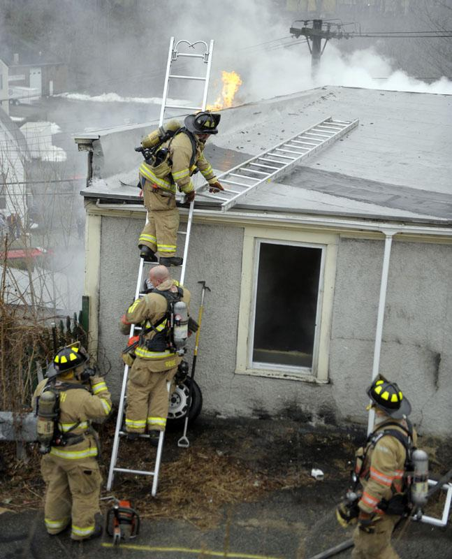 Norwich Firefighters head to the roof to ventilate the building as they battle a fire at 18 Grove St. Wednesday, March 6, 2013.