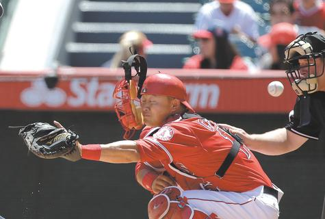 Angels catcher Hank Conger gets his mask knocked off by a foul ball in the first inning of Sunday's game against the Tigers at Anaheim, Calif.