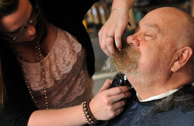 Mike Tirone, a retired City of Norwich firefighter, has his full beard shaved off during the