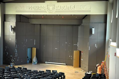 An employee of Shawmut Design and Construction paints a former Coast Guard training lecture hall Wednesday as renovations near completion for a new student center at the University of Connecticut's Avery Point campus in Groton. Contractors uncovered a frieze with the words 'Semper Paratus,' the Coast Guard motto, which is Latin for 'Always Ready.'
