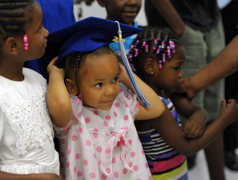 Alayja Biggs, 3, of Norwich, dons her aunt's mortar board after commencement at Three Rivers Middle College in Norwich, Wednesday, June 19, 2013.