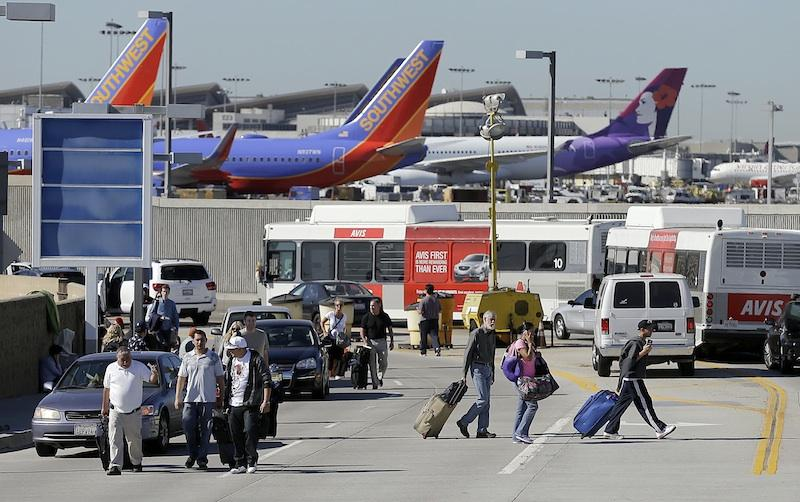 Passengers walk with their luggage leaving the Los Angeles International Airport on Friday Nov. 1, 2013. A suspected gunman was in custody Friday following a shooting at Los Angeles airport that left multiple people wounded and disrupted flights nationwide.