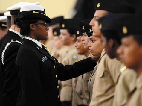 Second Platoon Commander Cadet Ensign Tamia Debarros-Cannon, left, checks one of her cadets' uniforms as U.S. Navy Capt. Carl Lahti, commanding officer at the U.S. Navy Submarine Base New London, inspects the cadets of the New London High School Navy Junior ROTC on Wednesday during the unit's annual inspection and pass and review.