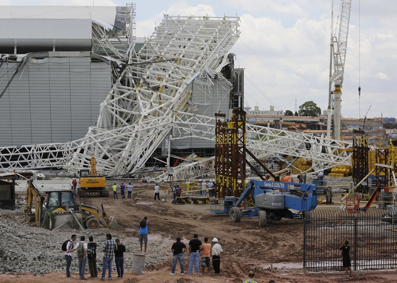 People stand in front of a metal structure that buckled on part of the Itaquerao Stadium in Sao Paulo, Brazil, Wednesday, Nov. 27, 2013. Part of the stadium that will host the 2014 World Cup opener in Brazil collapsed on Wednesday, causing significant damage and killing three people, authorities said.