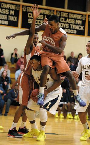 Hartford Capital defender Hassan Daniels, top, lands on Ledyard's Darnay Gray while Gray  pump-fakes his the way to the basket during Monday night's game. The Colonels won their fifth straight game be defeating Capital 73-57.