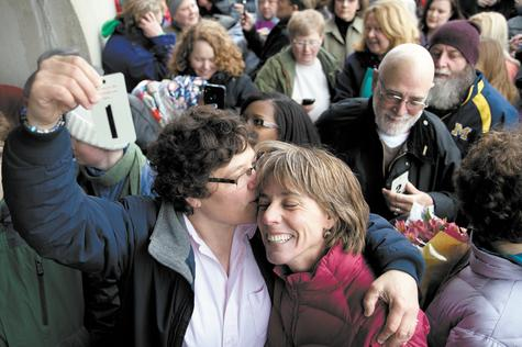 Elizabeth Patten, left, holds up the first marriage ticket to marry her partner Johnnie Terry in front of the Washtenaw County Clerk's office in Ann Arbor, Mich., on Saturday.