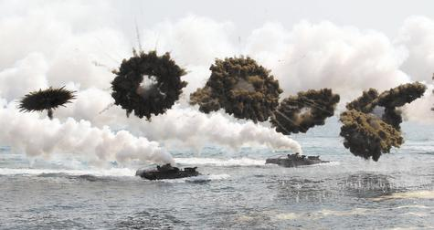 South Korean marine LVT-7 landing craft make their way to shore through smoke screens during joint U.S.-South Korea military exercises Monday in Pohang, South Korea. South Korea said North Korea has announced plans to conduct live-fire drills near the rivals' disputed western sea boundary. The drills Monday come after an increase in threatening rhetoric from Pyongyang and a series of rocket and ballistic missile launches in an apparent protest against the annual military exercises by Seoul and Washington.