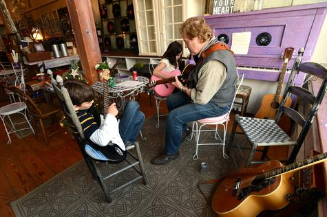 Dan Stevens works with Dante Occhipinti, 10, left, and Delaney Gagnon, 9, right, who are taking music lessons during an after-school guitar workshop at Nightingale's Acoustic Cafe in Old Lyme.