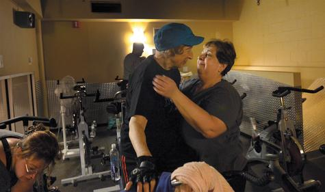 Alice Andrews, left, gets a hug from Bonnie McNichol of Niantic after the two completed a full hour of spinning class Thursday at Work Out World in Groton.
