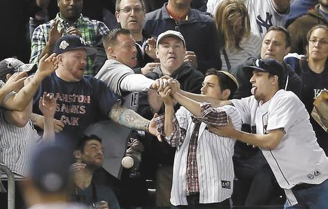 Red Sox and Yankee fans in left field battle for a baseball hit by Carlos Beltran of the Yankees for a two-run homer in the third inning of Sunday's game at Yankee Stadium in New York.
