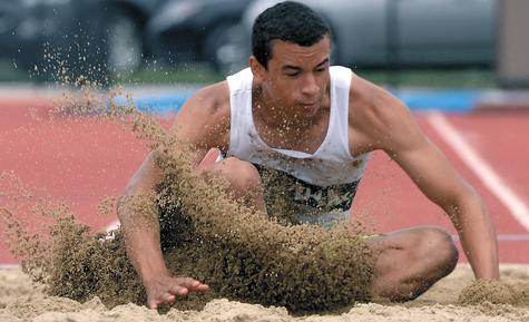 Ledyard's Joe Carter scatters sand while landing in the long jump pit during Tuesday's opening day of the CIAC decathlon championship at Coast Guard. Carter won the event in 20 feet, 9 1/4 inches, but trails Fitch's Taylor Latham 3,529-3,249 heading into the final five events today at 11 a.m.