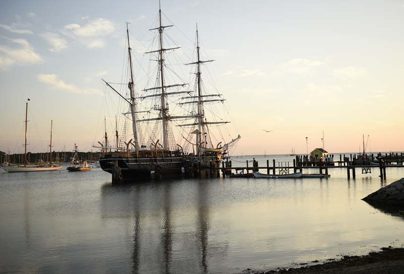 Sunrise lights the historic whaleship Charles W. Morgan docked at Tisbury Wharf in Vineyard Haven Harbor Wednesday, June 25, 2014, prior to its departure to New Bedford.