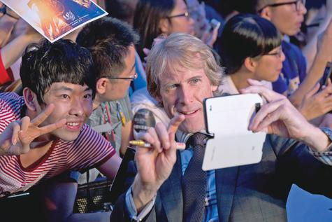 Director Michael Bay, front right, takes mobile phone photos for a Chinese fan at the premiere of 'Transformers: Age of Extinction' in Beijing, China.