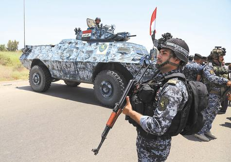 Iraqi federal policemen patrol Saturday in Baghdad's Abu Ghraib suburb. Iraqi troops backed by helicopter gunships launched an operation Saturday aimed at dislodging Sunni militants from the northern city of Tikrit, one of two major urban centers they seized in recent weeks in a dramatic blitz across the country.