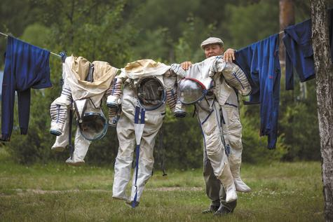 An employee of Russian Space Training Center hangs out to dry space suits of Russian cosmonaut Anatoly Ivanishin, NASA flight engineer Kathleen Rubins, and Japanese space agency flight engineer Takuya Onishi after a training session Wednesday near Noginsk, Russia. The training was intended to simulate the capsule landing on water. Ivanishin, Onishi and Rubins are being trained for a future mission to the International Space Station.