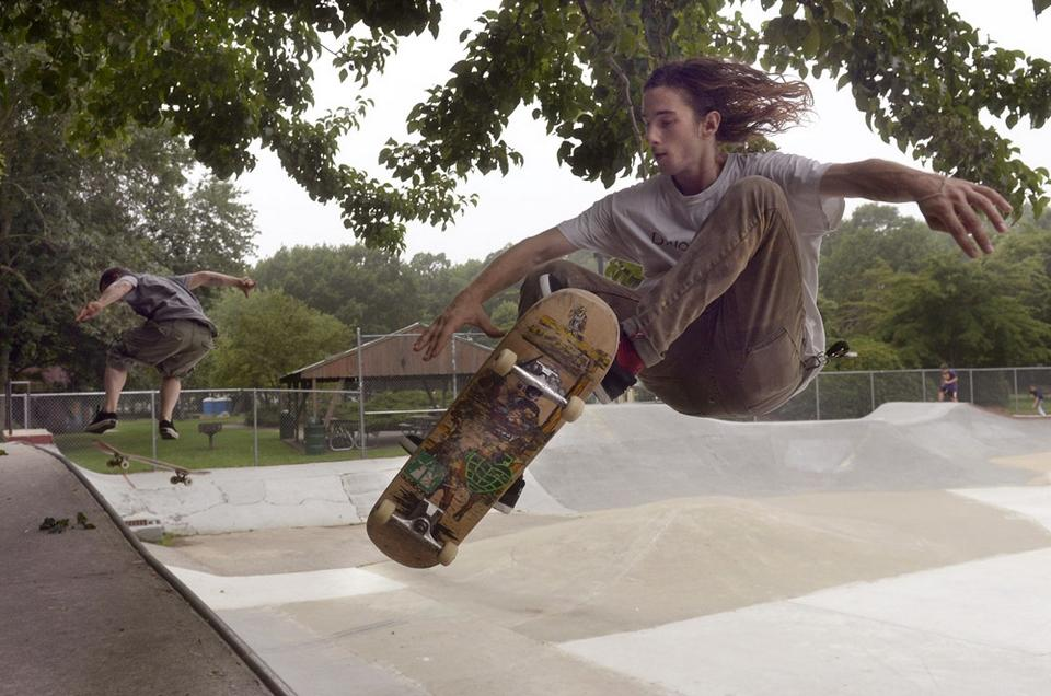 Kevin Phelps, foreground, 21, of Groton, practices a front-side air maneuver at the Groton Skate Park Tuesday, July 15, 2014.