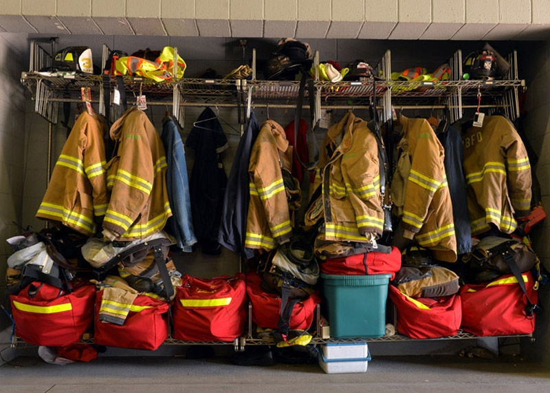 Firefighter coats and safety equipment hang in the apparatus bay at the Poquonnock Bridge Fort Hill Fire Station Friday morning, July 25, 2014. The coat, second from right, belonged to a firefighter who lost his job in this round of layoffs.