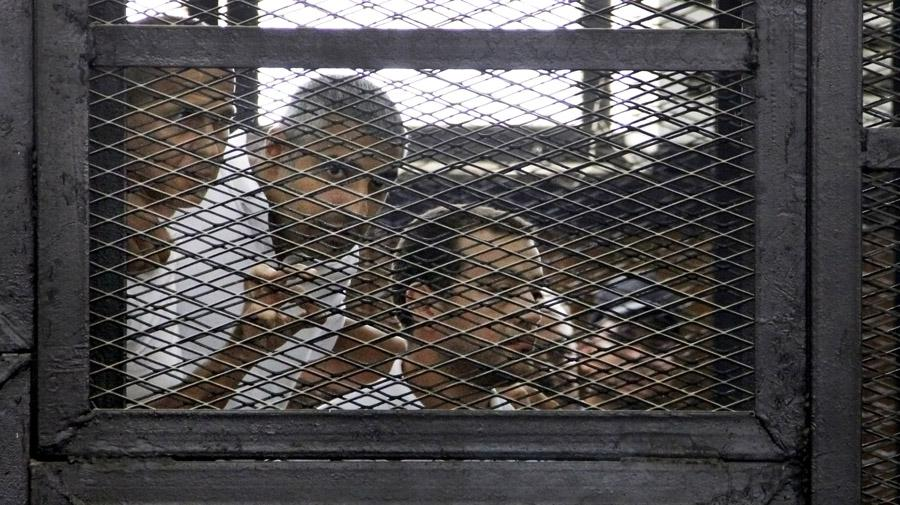 From left, Australian correspondent Peter Greste, Canadian-Egyptian acting bureau chief of Al Jazeera Mohamed Fadel Fahmy, and Egyptian producer Baher Mohammed, appear in a defendant's cage in a courtroom in Cairo, Egypt, Monday, June 23, 2014.