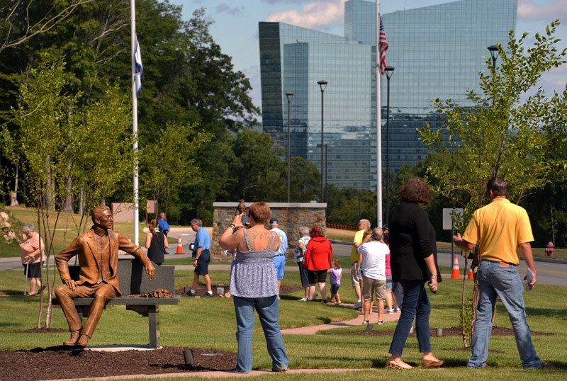 People walk the path following the dedication ceremony for their garden walk honoring the Mohegan chiefs of the 20th century in front of the Mohegan Community and Government Center Friday, Aug. 15, 2014.
