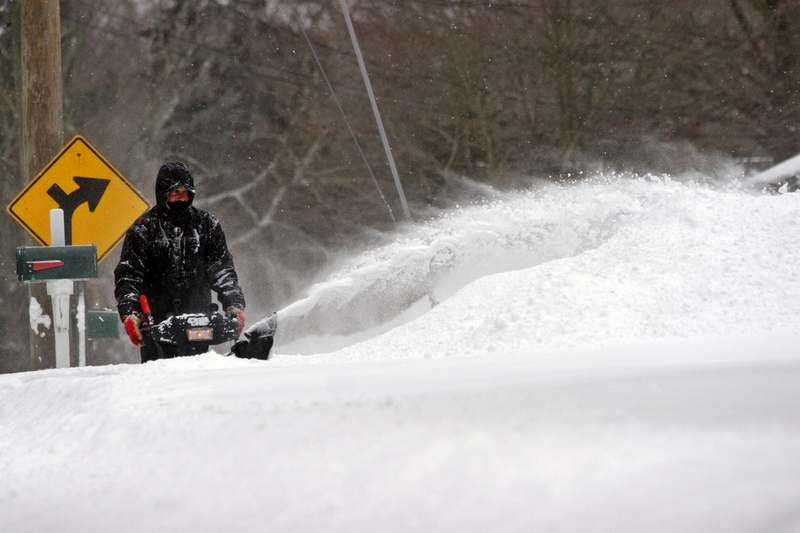 Jay Moreau uses a snow blower to clear the walkway in front of his home, along Rope Ferry Road in Waterford as the snowstorm blankets the region Tuesday, Jan. 27, 2015.