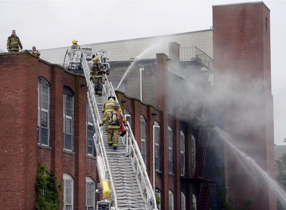 Firefighters battle a fire in the upper floors of the former mill building at 21 River Rd. in Pawcatuck, Wednesday, May 27, 2015. (Sean D. Elliot/The Day)