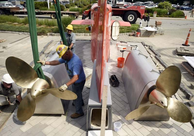 Crews from the Submarine Force Library and Museum and contractor LBI, Inc., put the finishing touches installing the Submarine NR-1 exhibit on the grounds of the museum in Groton Friday, June 12, 2015. (Sean D. Elliot/The Day)