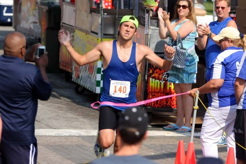 Nick Migani, of Griswold, breaks the tape as he runs down State Street to win the Sailfest Charter Oak 5K race, Sunday, July 12, 2015, in New London. (Steven Frischling/Special to The Day)